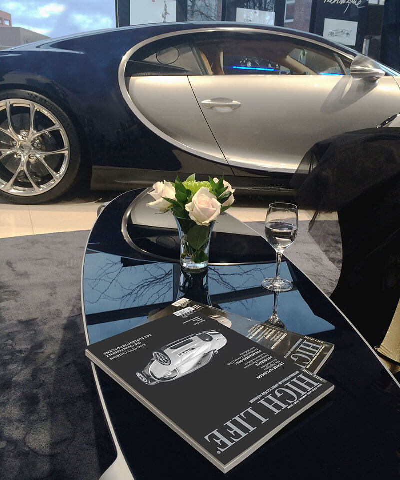 HIGH LIFE magazines in front of a Bugatti Chiron luxury car