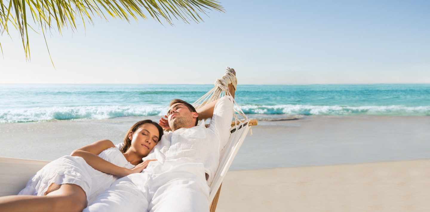 Couple in a hammock at the beach under palm trees